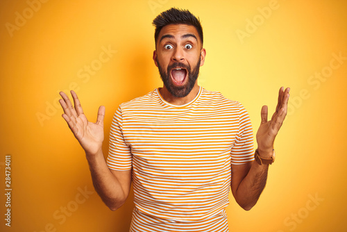 Young indian man wearing t-shirt standing over isolated yellow background celebrating crazy and amazed for success with arms raised and open eyes screaming excited Wallpaper Mural