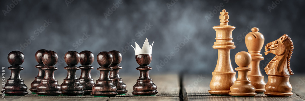 Fototapeta  Small Courageous Pawn With Fake Paper Crown Costume Leading Others Into Battle Against The Enemy - Business Entrepreneur / Leadership Concept