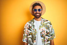 Indian Man On Vacation Wearing Floral Shirt Hat Sunglasses Over Isolated Yellow Background With A Happy And Cool Smile On Face. Lucky Person.