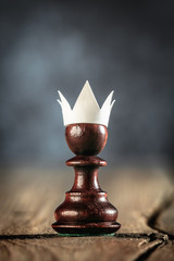 Small Ambitious Pawn With Fake Paper Crown Costume On Wooden table - Business Entrepreneur Concept