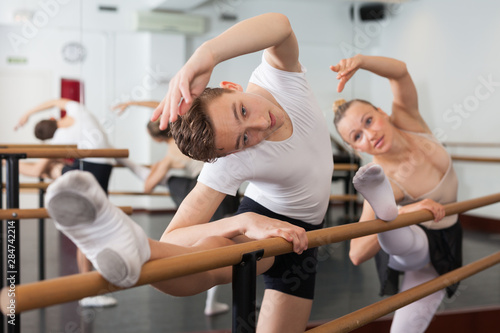 Fotografía  Graceful woman and young man pose in hall with ballet bar