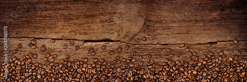 fresh-roasted-coffee-beans-natural-dark-oak-wood-panorama-wide-plank-wooden-closeup-macro-background