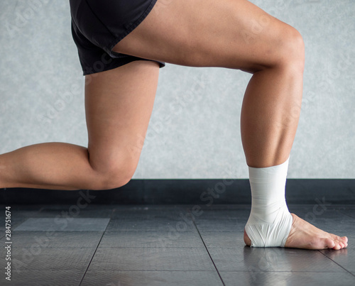 Photo Athlete mid lunge with an ankle tape job