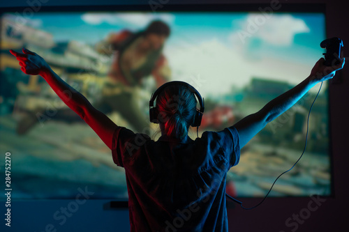 A girl gamer plays games with a gamepad, joystick on a large screen, with bright light and a dark room Wallpaper Mural