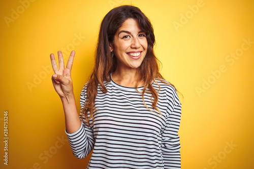 Young beautiful woman wearing stripes t-shirt standing over yelllow isolated background showing and pointing up with fingers number three while smiling confident and happy Fototapete