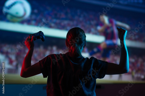 Soccer game, girl gamer playing a game in football headphones on a big screen, with bright light and a dark room Canvas Print