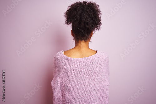 Young african american woman wearing winter sweater standing over isolated pink background standing backwards looking away with crossed arms