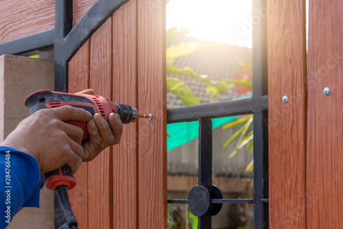 Man hand using impact driver to fix the wood panel with steel. Lerretsbilde
