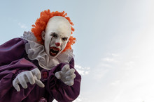 Scary Clown Against The Sky. A Teenage Boy In A Suit Like A Red-haired Pennywise Opened His Mouth With Sharp Teeth Close-up. Cosplay IT For Carnival Or For Halloween. Copy Space.