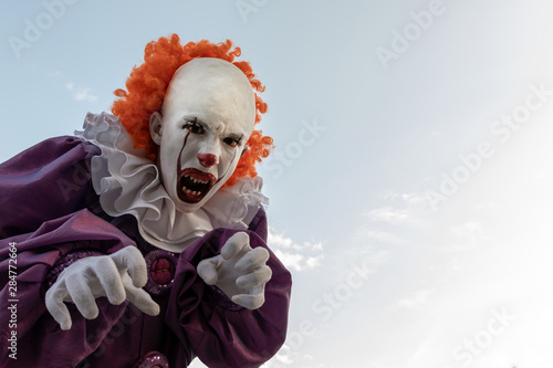 Scary clown against the sky Fototapeta