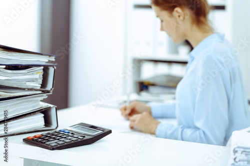 Calculator and binders with papers are waiting to be processed by business woman or bookkeeper back in blur Canvas Print