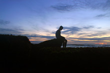 Blurry Image Concept Background Of Young Boy Silhouette Sits Alone Head Down On Sea Rock In Sadness. Beautiful Dramatic Sunset Sky Colors And The Rocky Beach Backgrounds.