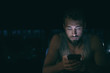 canvas print picture Dark night man looking at mobile phone screen texting late at night awake in bed insomnia or outside in city with skyline background. Serious looking guy depressed addicted to social media.