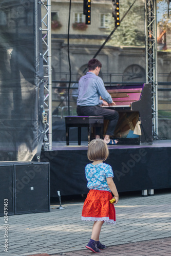 dziewczynka zasłuchana w muzyce spogląda na pianistę na plenerowym koncercie  - fototapety na wymiar