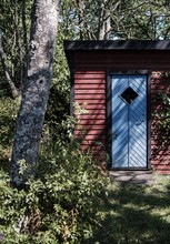 Vertical Shot Of A Blue Door Of A Red Small Wooden Barn Next To A Tree In A Forest