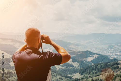 Fotografia  Man standing on of stump in summer mountains