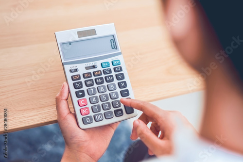 Fototapeta Woman holding and press calculator to calculate income expenses and plans for spending money on home office. obraz