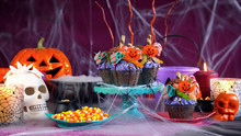 Happy Halloween Candyland Drip Cake Style Cupcakes With Lollipops And Candy In Party Table Setting, With Copy Space