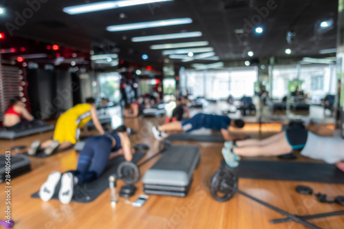 Poster Fitness Blur Fitness class with group of people excercising with barbell, dumbbell