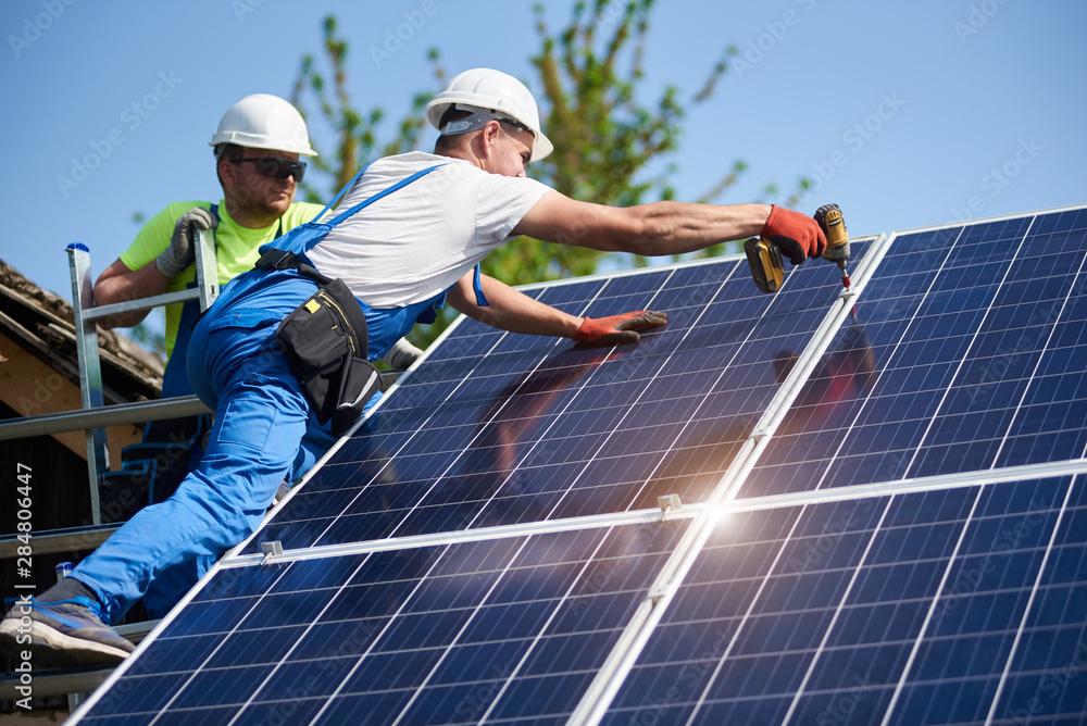 Fototapeta Two workers technicians installing heavy solar photo voltaic panels to high steel platform. Exterior solar system installation, alternative renewable green energy generation concept.
