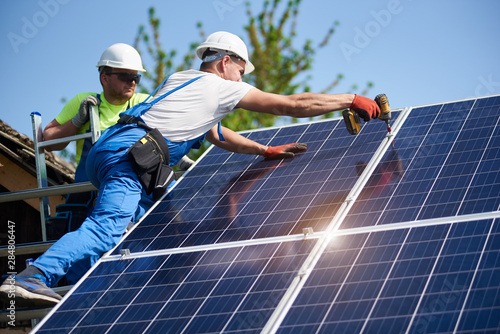 Fotografía  Two workers technicians installing heavy solar photo voltaic panels to high steel platform