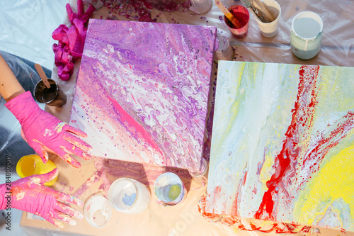 Fotografia, Obraz Creative woman painter teaching three female student creating fluid acrylic abstract painting in art therapy class, with table full of bottle with defferent paint colors