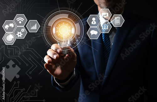 Fotografia, Obraz  innovation and technology, businessman holding holding tablet with lighting bulb