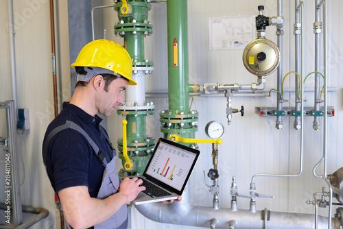 Fényképezés Arbeiter bei Instandhaltung einer modernen Industrieanlage - Kontrolle und Aufna