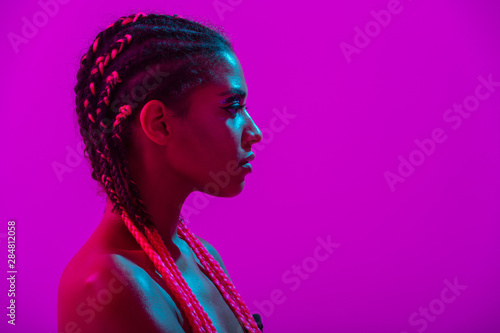 Fototapeta Young african naked woman posing isolated over purple neon lights wall background obraz na płótnie