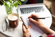 Female Hands Holding Notebook And Pen While Making Working Notes By Table