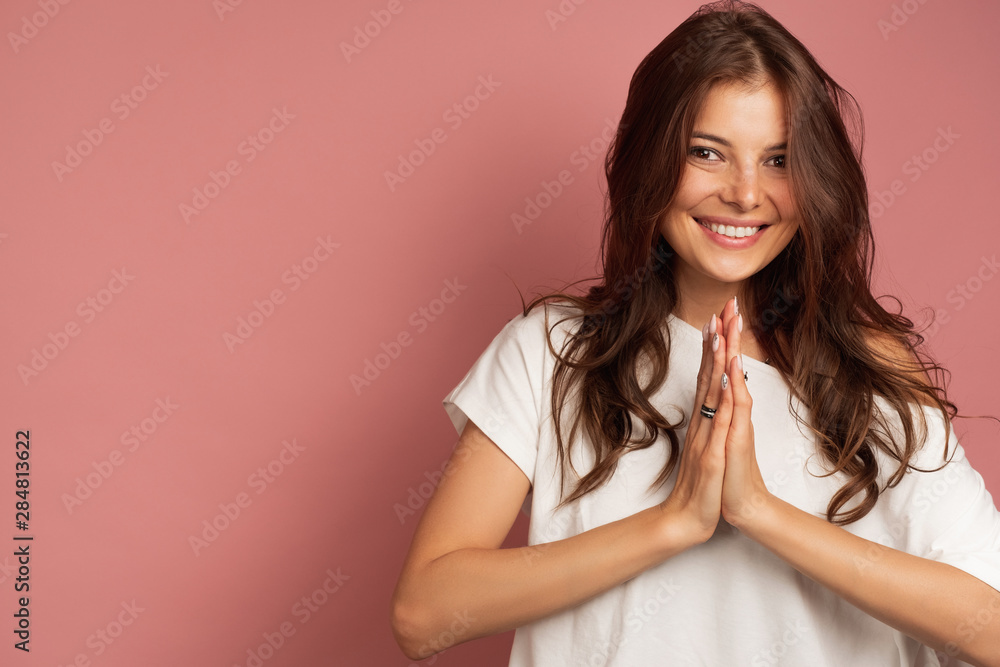 A girl in a white top is standing on a pink background smiling at the camera with her palms pressed to each other.