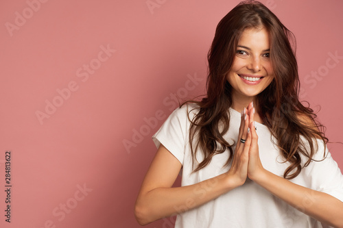 A girl in a white top is standing on a pink background smiling at the camera with her palms pressed to each other Tablou Canvas
