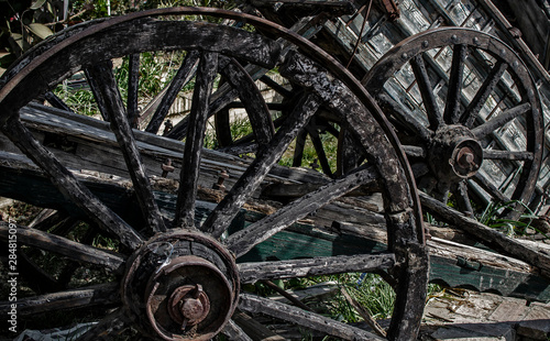 Spoed Fotobehang Oude verlaten gebouwen Closeup of old carriage wheels