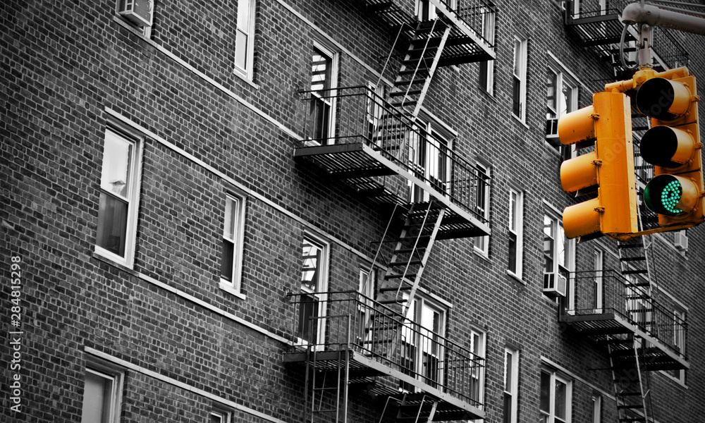 Fototapeta Green traffic light in New York city with an old urban building with fire escape stairs in the background. Selective color yellow. Black and white.