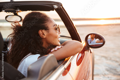 Image of young pretty woman looking aside while riding in convertible stylish car by seaside