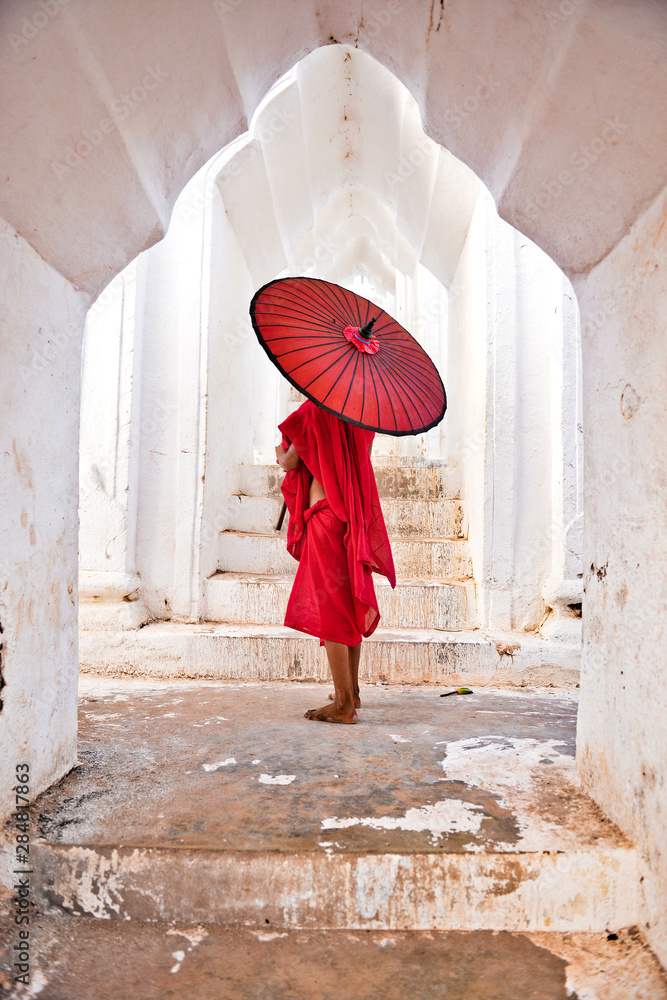 Fototapeta novice buddhist monks with red traditional robes holding red umbrellas walking in a white buddhist temple in myanmar