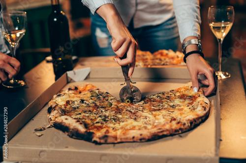 Tuinposter Pizzeria closeup of woman cutting pizza .