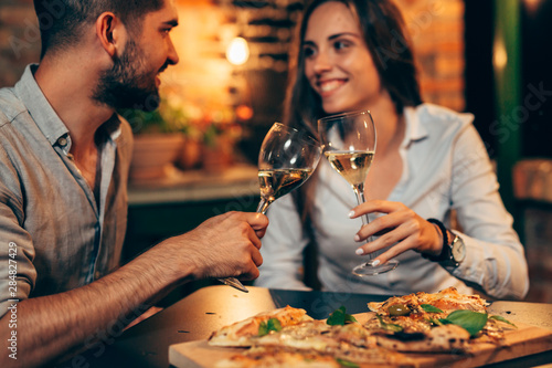 Fotografía young couple making toast with wine, at home in garden, evening scene