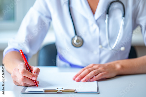 Stampa su Tela  A doctor with a stethoscope writes out a medical prescription during a medical consultation