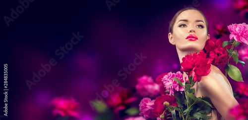 Beauty girl with purple, red, pink peony flowers portrait. Beauty high fashion model woman with peony flowers closeup