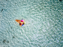 Aerial View Of Beautiful Caucasian People Adult Woman Tourist Lay Dawn And Relaxing On A Trendy Coloured Lilo With Transparent And Clean Tropical Sea Water Around - Concept Of Summer Vacation