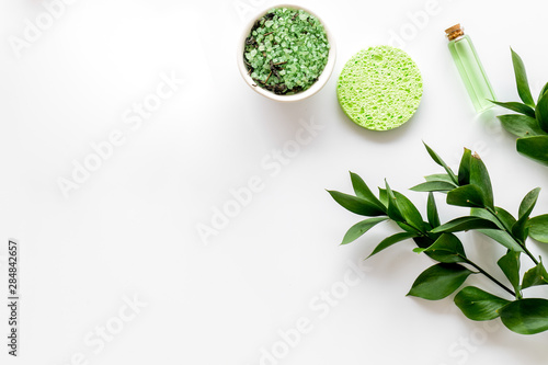 Cosmetics for face with sponge, salt, lotion from herbs on white background top view copyspace
