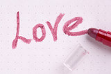 "The word love written by lipstick on a sheet of paper. Lipstick and the word ""Love""."