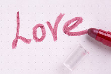 """The Word Love Written By Lipstick On A Sheet Of Paper. Lipstick And The Word """"Love""""."""