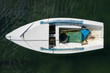 white wooden fishing boat anchored in the sea, top view