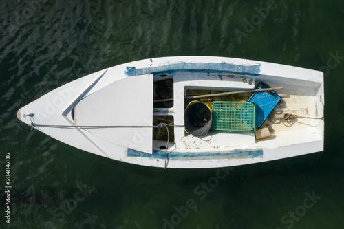 Fototapeta white wooden fishing boat anchored in the sea, top view obraz na płótnie