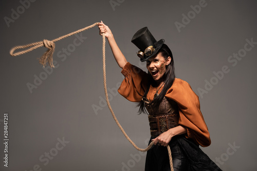 Cuadros en Lienzo attractive steampunk girl in top hat holding lasso and screaming isolated on gre