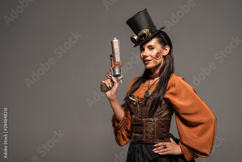 Fotografering smiling steampunk woman in top hat with goggles standing with hand on hip and ho