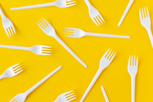 White Plastic Forks On Yellow Background. Flatlay.