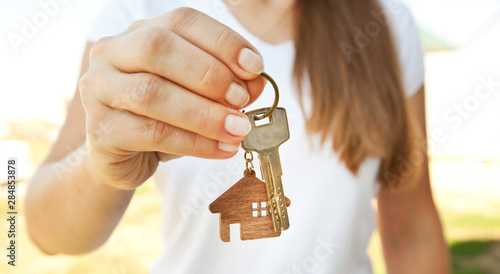 Cuadros en Lienzo The mental key from door with wooden trinket in shape of house in woman's hand